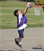 young boy dunking basketball